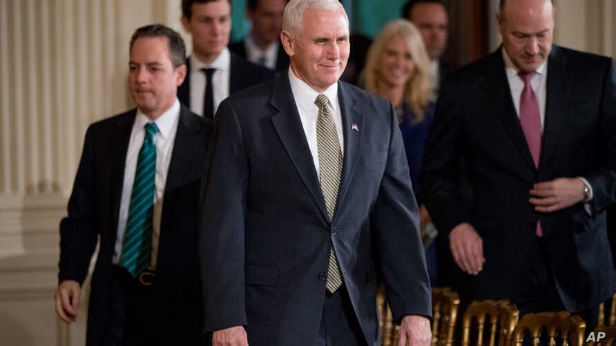 Vice President Mike Pence, center, arrives in the East Room of the White House in Washington, Feb. 13, 2017.
