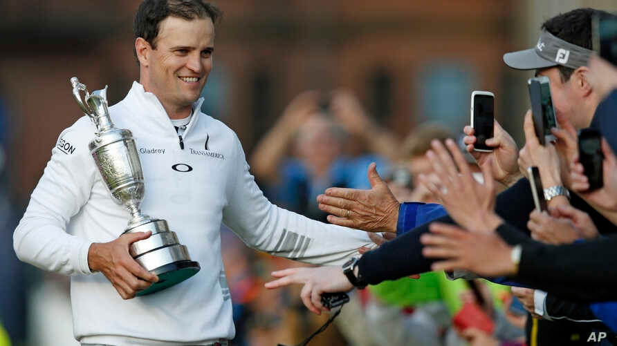United States' Zach Johnson celebrates with members of the public as he holds the trophy after winning a playoff after the final round at the British Open Golf Championship at the Old Course, St. Andrews, Scotland, July 20, 2015.
