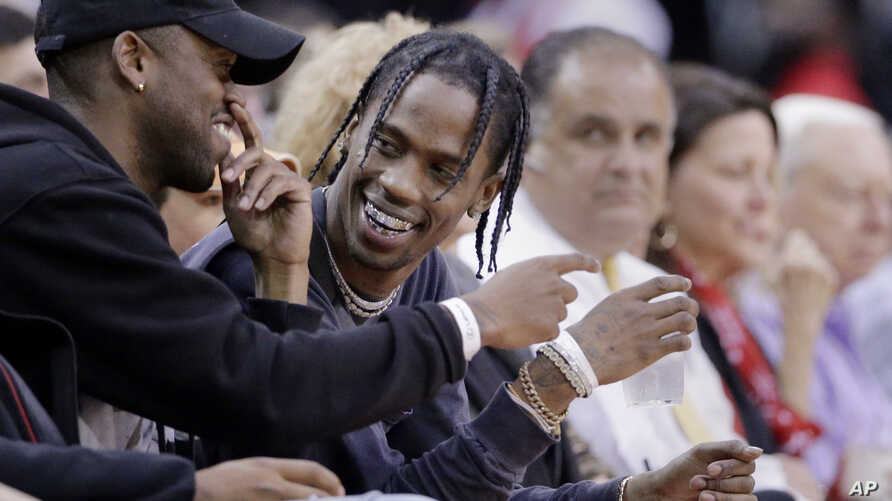 FILE - Rap artist Travis Scott, center, reacts during an NBA basketball game between the Houston Rockets and Denver Nuggets in Houston, April 5, 2017.