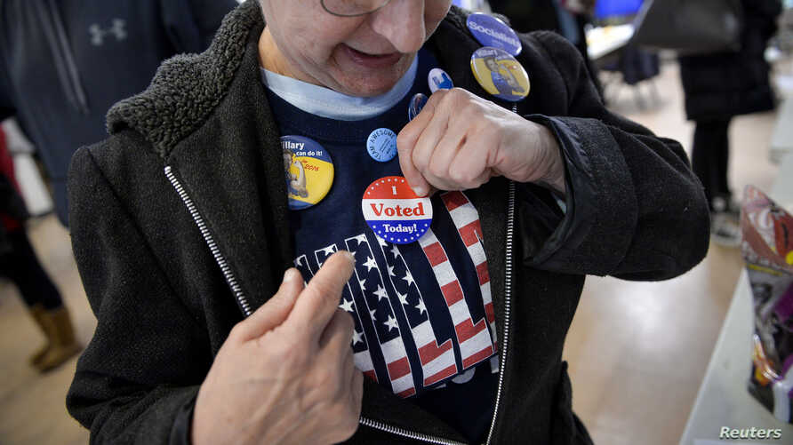 """A voter puts on an """"I voted"""" sticker during the U.S. presidential election in Philadelphia, Pennsylvania, Nov. 8, 2016."""