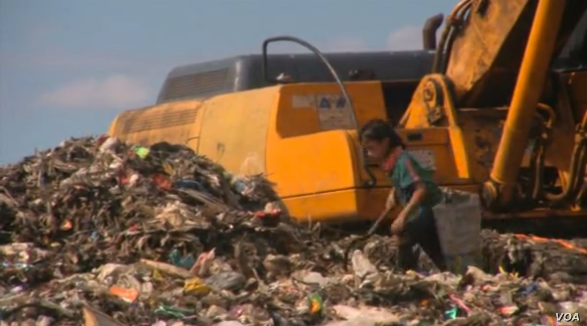 Men, women, and children dig through mountains of trash to earn money by collecting plastic and glass bottles for recycling.