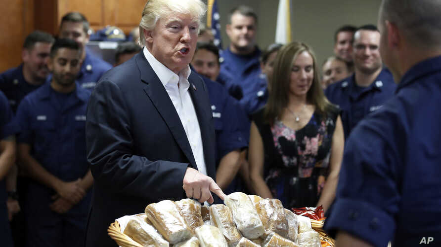 President Donald Trump prepares to hand out sandwiches to members of the U.S. Coast Guard at the Lake Worth Inlet Station, in Riviera Beach, Fla., on Thanksgiving, Nov. 23, 2017.