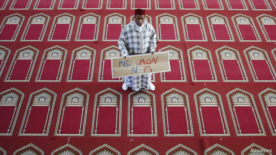 """Muslim Khaloar Abdarahim holds a placard which reads """"Not in my name"""" as he poses inside the Arrahma Mosque after Friday prayers in Nantes, western France, Sept. 26, 2014 after a gathering to pay tribute to French mountain guide Herve Gourdel who was"""