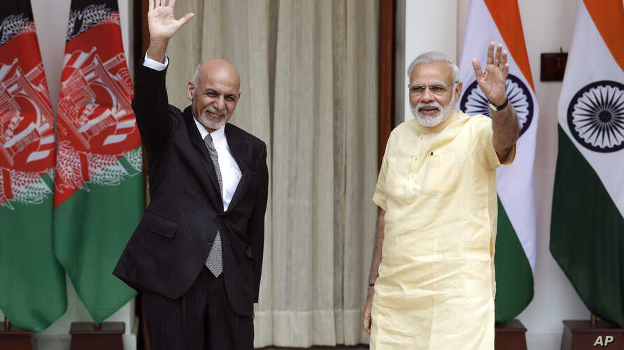 Indian Prime Minister Narendra Modi, right, and Afghan President Ashraf Ghani wave at the media before a meeting in New Delhi, India, Sept. 14, 2016. President Ghani is on a two-day visit to India.