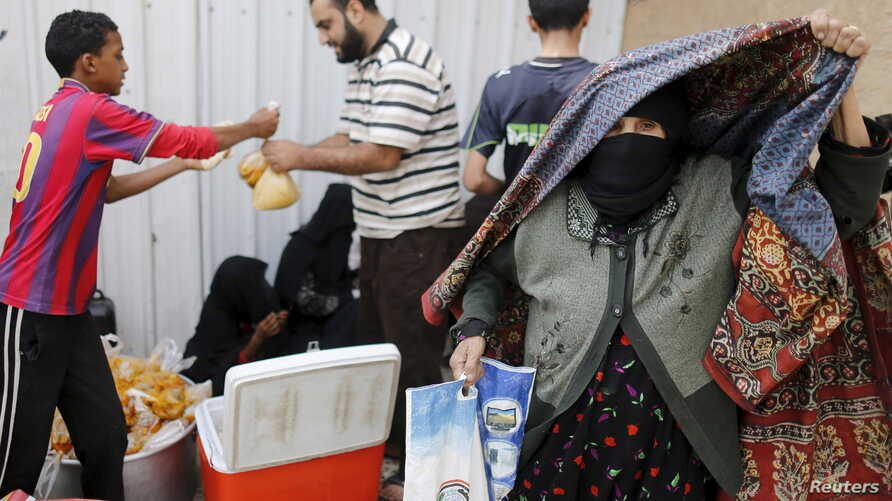 An elderly woman leaves a charity food assistance center after receiving her ration in Yemen's capital Sanaa, July 1, 2015.