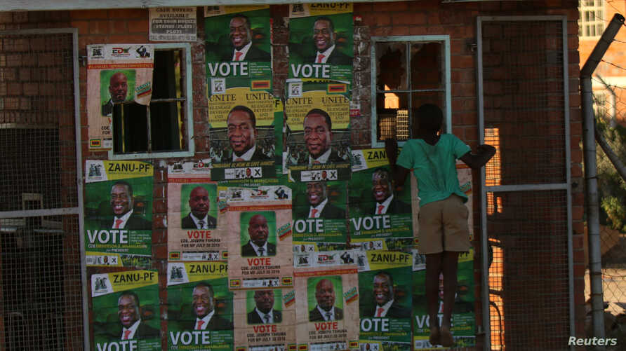 FILE - A boy plays next to election posters in Bulawayo, Zimbabwe, June 23, 2018.