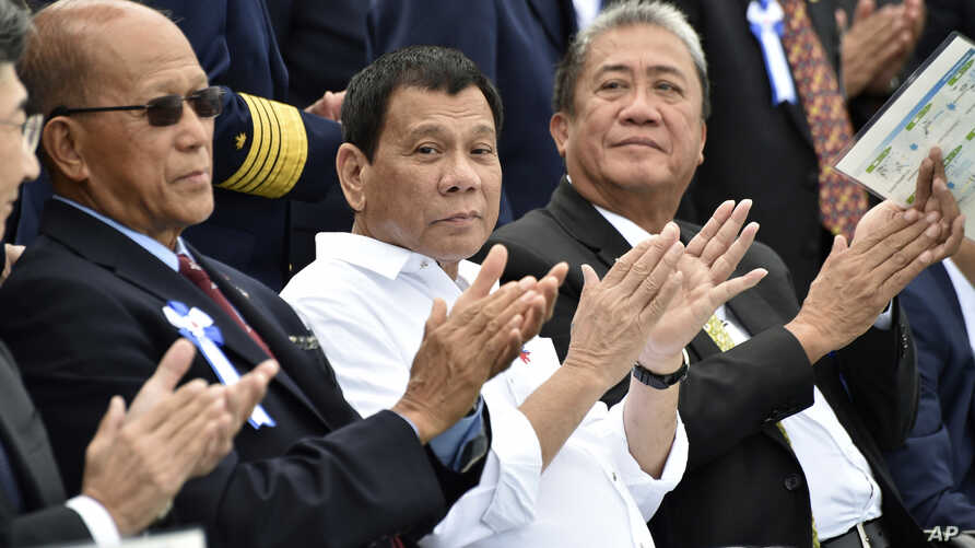Philippine President Rodrigo Duterte, center, accompanied by Transportation Secretary Arthur Tugade, right, and Defense Secretary Delfin Lorenzana, left, clap their hands at the end of Japan's coast guard drills in Yokohama, Oct. 27, 2016.