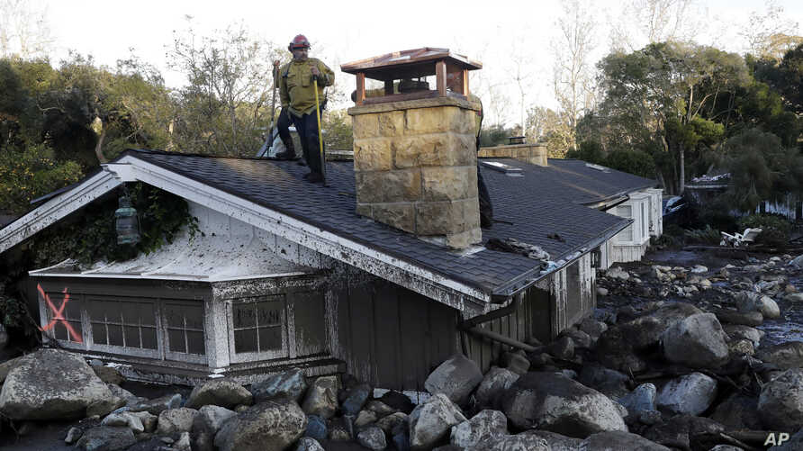 A firefighter stands on the roof of a house submerged in mud and rocks in Montecito, California.