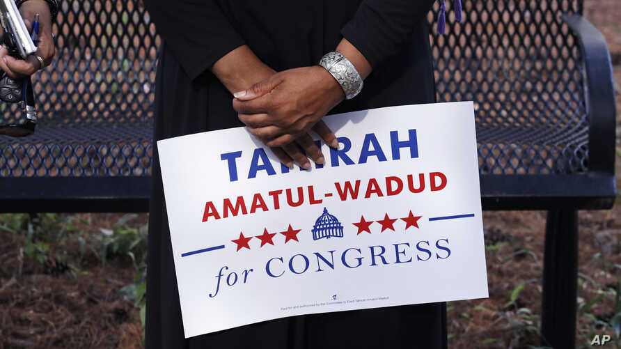 Attorney Tahirah Amatul-Wadud, who is challenging incumbent U.S. Rep. Richard Neal, D-Mass., holds a campaign sign as she meets residents of an apartment complex in Springfield, Mass., Monday, June 18, 2018.