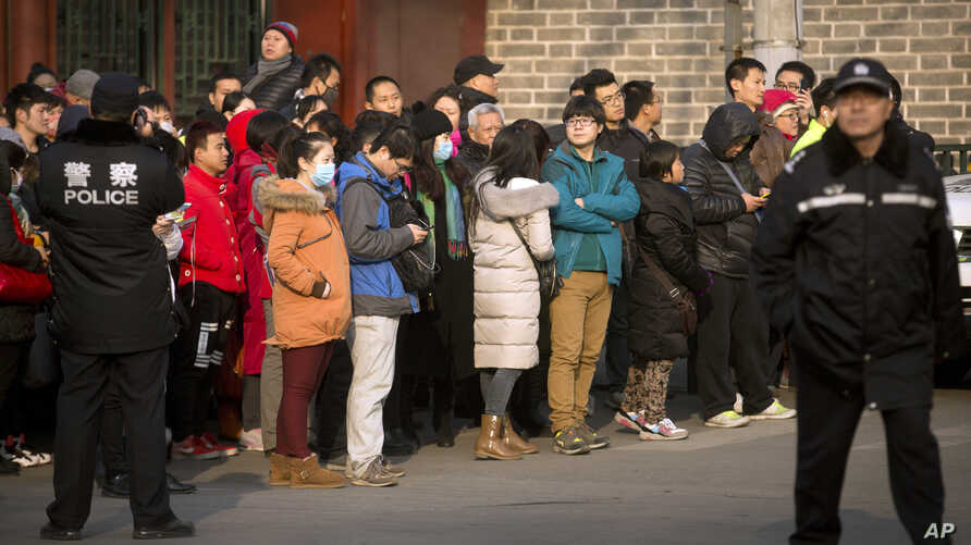 FILE - In this Jan. 1, 2016, file photo, Chinese policemen watch as depositors from Ezubao gather outside the State Bureau for Letters and Calls Reception Division office in Beijing. China's policy ministry says it investigated 380 online lenders and