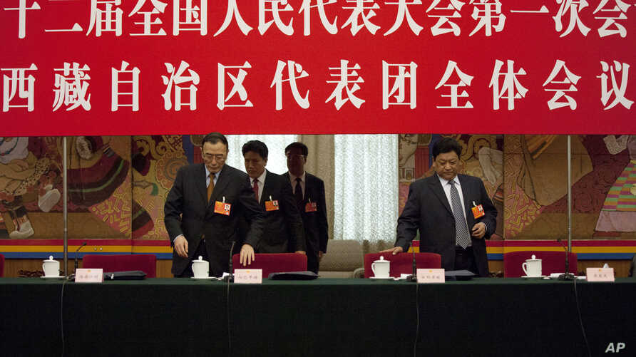 Champa Phuntsok, chairman of the Tibetan Autonomous Region's people's congress standing committee, left, and Tibet's governor Padma Choling, right, take their seats during a National People's Congress Tibetan delegate group's discussion session in Be