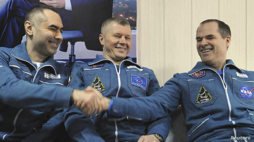 International Space Station (ISS) crew members Russian cosmonauts Evgeny Tarelkin (L) and Oleg Novitskiy (C) and U.S. astronaut Kevin Ford sit together at Kustanay Airport after they landed near the town of Arkalyk, Mar. 16, 2013.