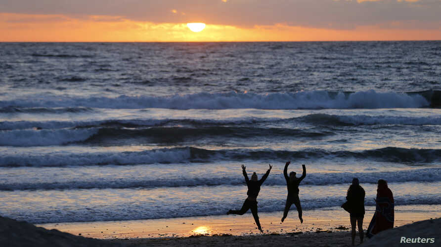 Teenagers pose while having their pictures taken with a phone as the sun sets in Encinitas, California March 31, 2014.