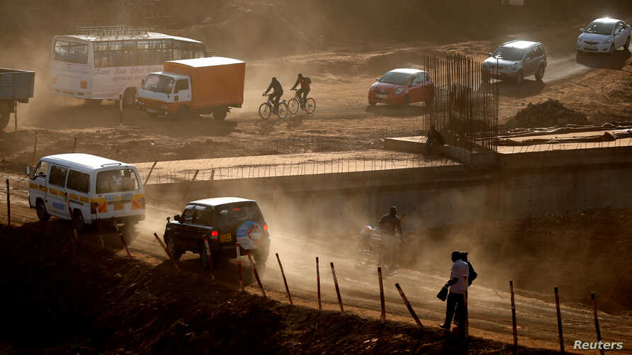 People and vehicles are seen on a road under construction in Nairobi, Kenya Jan. 25, 2017.