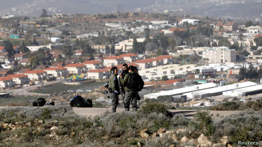 Israeli paramilitary police stand together during an evacuation by the Israeli forces of Jewish settlers from Amona, an illegal outpost in the Israeli-occupied West Bank, Jan. 3, 2019.