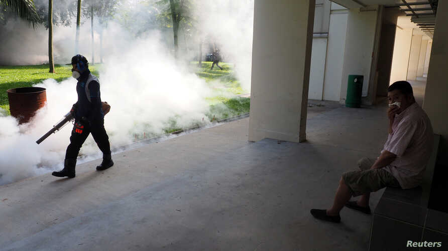 A resident shields his nose as pest control officer carry out fogging in the Aljunied Crescent cluster in Singapore, Sept. 3, 2016 in this photo taken by Antara Foto.