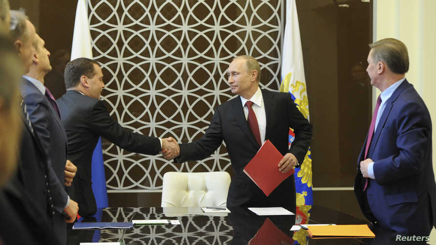Russian President Vladimir Putin shakes hands with Prime Minister Dmitry Medvedev during a Security Council meeting in Sochi March 13, 2014