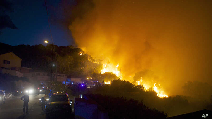 Firefighters work to control a forest fire on a hillside near the village of Ortale, Corsica island, France, July 24, 2015.