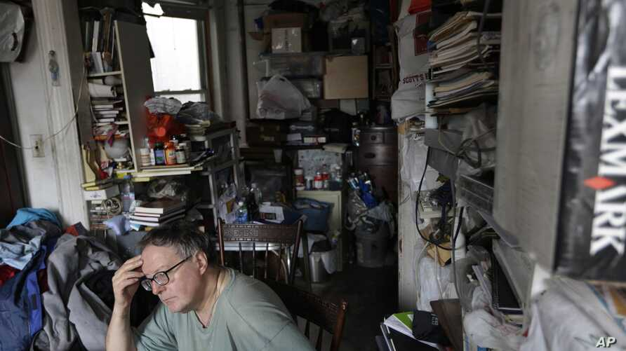 FILE - A man pictured in his cluttered home.