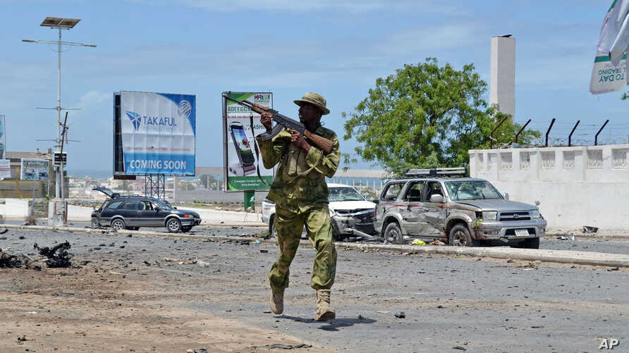 An armed Somali soldier runs to fight during an attack on Somalia's parliament in Mogadishu, May 24, 2014.