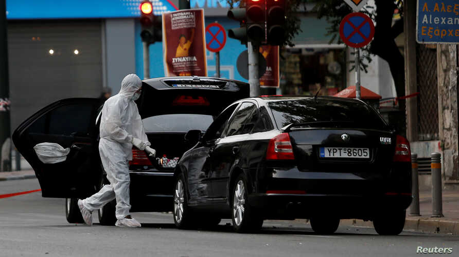 A forensic officer inspects the car of former Greek prime minister and former central bank chief Lucas Papademos following the detonation of an envelope injuring him and his driver, in Athens, Greece, May 25, 2017.