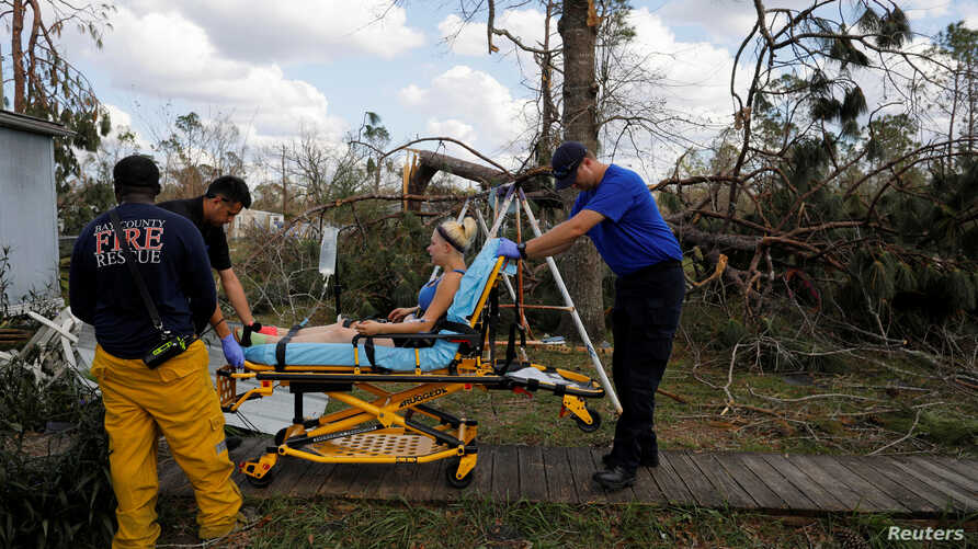 Medics take Angelena Sawyer to the ambulance for her untreated acute appendicitis during a wellbeing check by a 50 Star Search and Rescue team following Hurricane Michael in Fountain, Florida, Oct. 17, 2018.