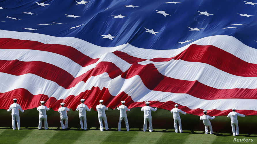 U.S. sailors unravel a huge American flag across the field during opening day ceremonies before the San Diego Padres host the Los Angeles Dodgers in their MLB National League baseball game in San Diego, California, April 9, 2013.