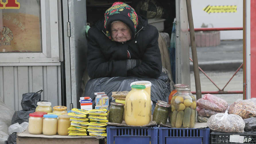 FILE - An elderly Ukrainian woman sells home made products  in downtown Kiev, Ukraine, Feb. 3, 2016.