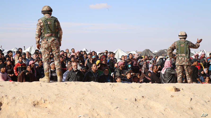 FILE - Syrian refugees wait to be approved to get into Jordan, in the Hadalat reception area, near the northeastern Jordanian border with Syria, and Iraq, near the town of Ruwaished, Jan. 14, 2016.