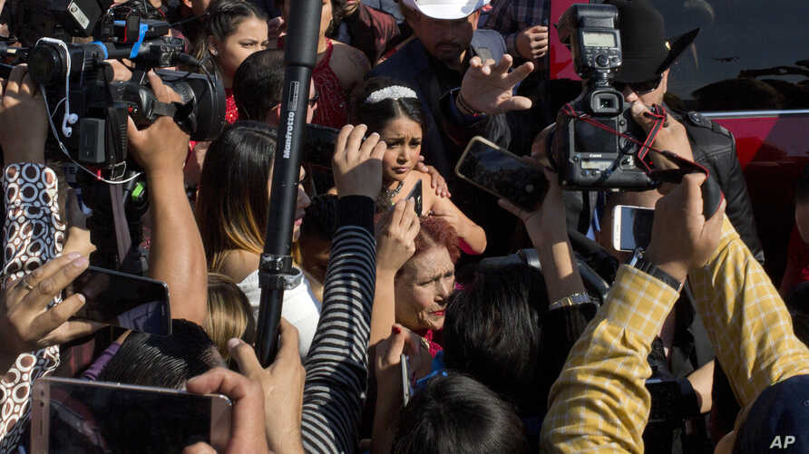 Rubi Ibarra arrives at the site of a Mass that is part of her down-home 15th birthday party, surrounded by a horde of journalists, in the village of La Joya, San Luis Potosi State, Mexico, Dec. 26, 2016.