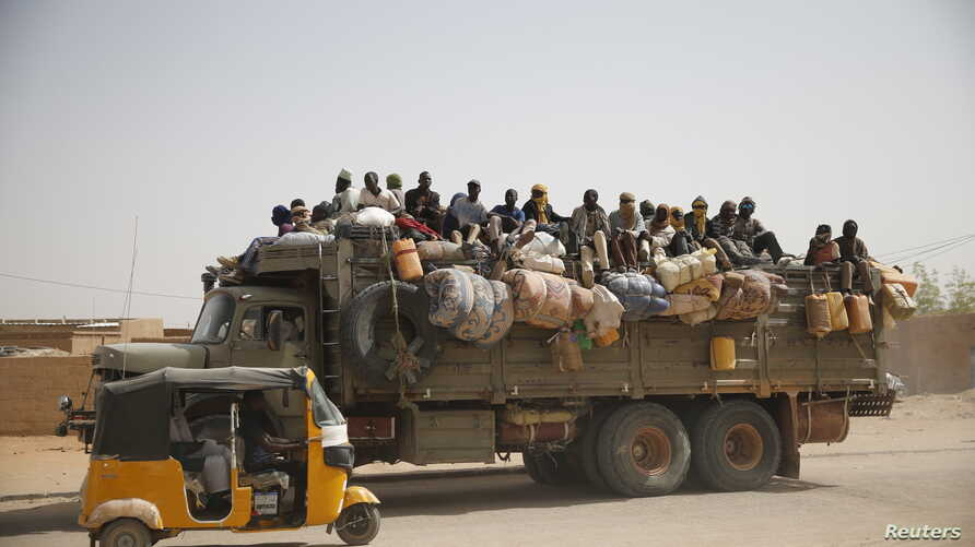 Migrants sit on their belongings in the back of a truck as it is driven through a dusty road in the desert town of Agadez, Niger, headed for Libya, May 25, 2015.