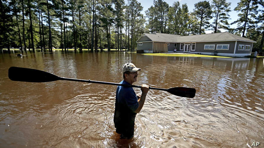 The home of Kenny Babb is surrounded by water as he retrieves a paddle that floated away while the Little River continues to rise in the aftermath of Hurricane Florence in Linden, N.C., Sept. 18, 2018.