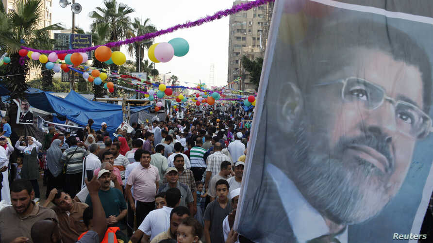 Members of the Muslim Brotherhood and supporters of deposed Egyptian President Mohamed Morsi hold a giant poster of him on the first day of the Eid al-Fitr, Cairo, August 8, 2013.