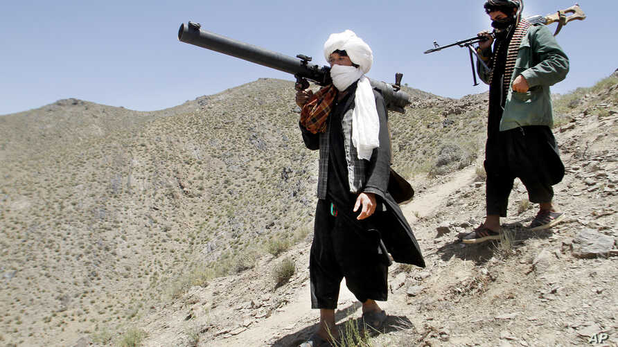 FILE - Afghan Taliban fighters are seen carrying weapons in a May 27, 2016, photo.