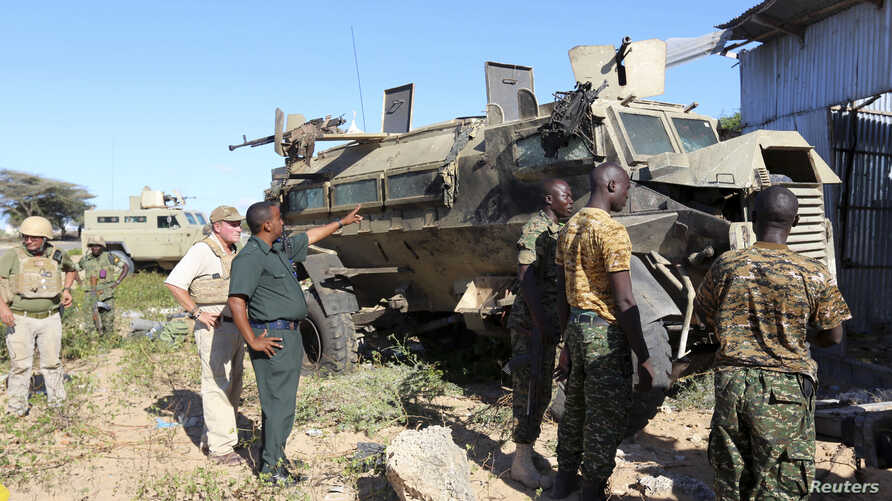 African Union troops stand next to an armored carrier targeted by suicide car bomb attackers while travelling in a convoy outside the capital, Mogadishu, Somalia, Sept. 8, 2014.