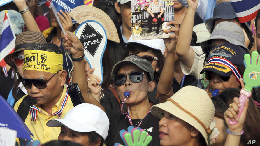 Anti-government protesters, one holds a picture of Thai King Bhumibol Adulyadej, chant slogans during a demonstration against an amnesty bill in Bangkok, Thailand, Nov. 11, 2013.