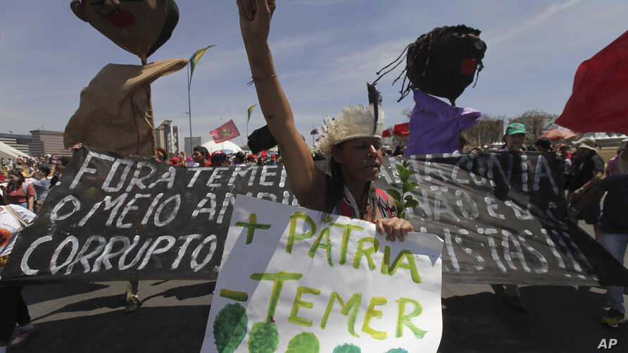 """A demonstrator carries a poster written in Portuguese """"More Motherland, Less Temer,"""" during a protest after an Independence Day military parade, in Brasilia, Brazil, Sept. 7, 2017. Michel Temer, the president of Brazil, is under investigation for pos"""