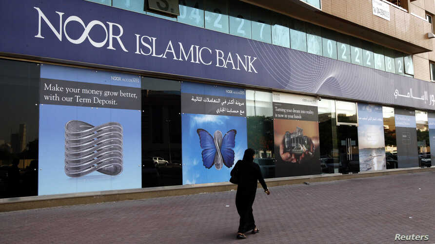 A woman walks past a branch of Noor Islamic Bank, which changed its name to Noor Bank in January 2014, in Dubai in 2010.
