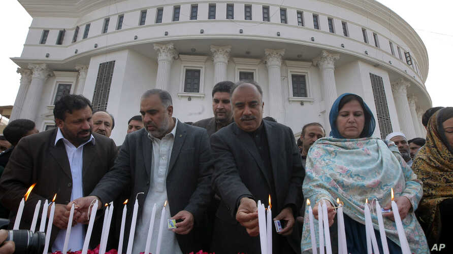 Pakistani lawmakers from provincial Khyber Pakhtunkhwa assembly light candle during a ceremony to mark second anniversary of a Taliban attack in 2014 on a school in Peshawar, Dec. 16, 2016.