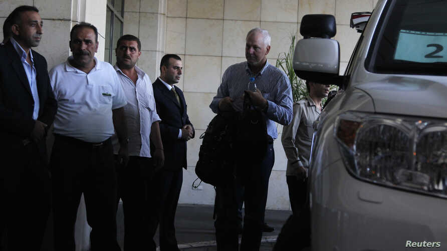 Ake Sellstrom (R), the head of a U.N. chemical weapons investigation team, arrives in Damascus August 18, 2013.