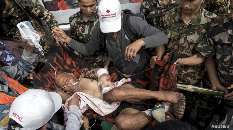Nepal military personnel and aid workers carry earthquake victim Buddha Gurung on a stretcher after he arrives by helicopter from his village in Pokkara airport, Nepal, April 30, 2015.