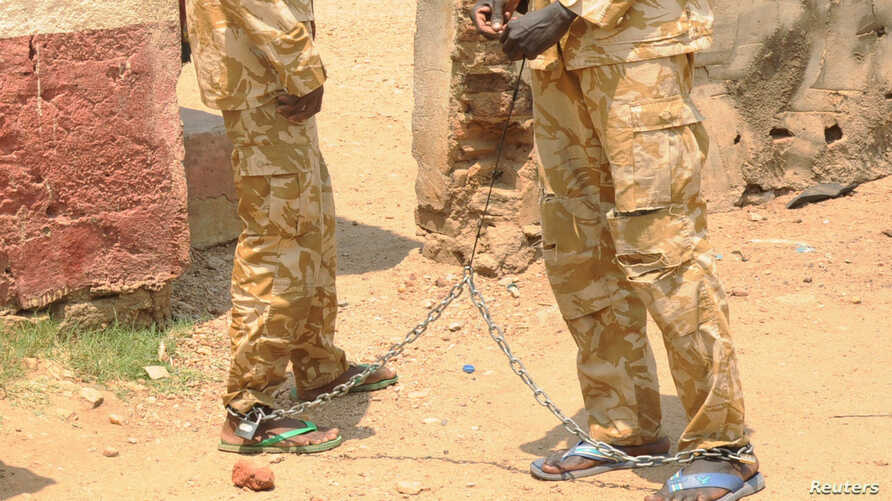 South Sudanese soldiers suspected of beating and raping civilians are chained together at the presidential guard unit, within the Sudan People's Liberation Army headquarters, after their arrest in Juba, March 3, 2017.