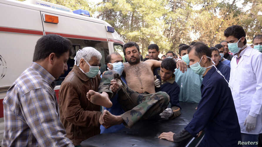 Residents and medics transport a Syrian Army soldier, wounded in what they said was a chemical weapon attack near Aleppo, to a hospital, March 19, 2013.