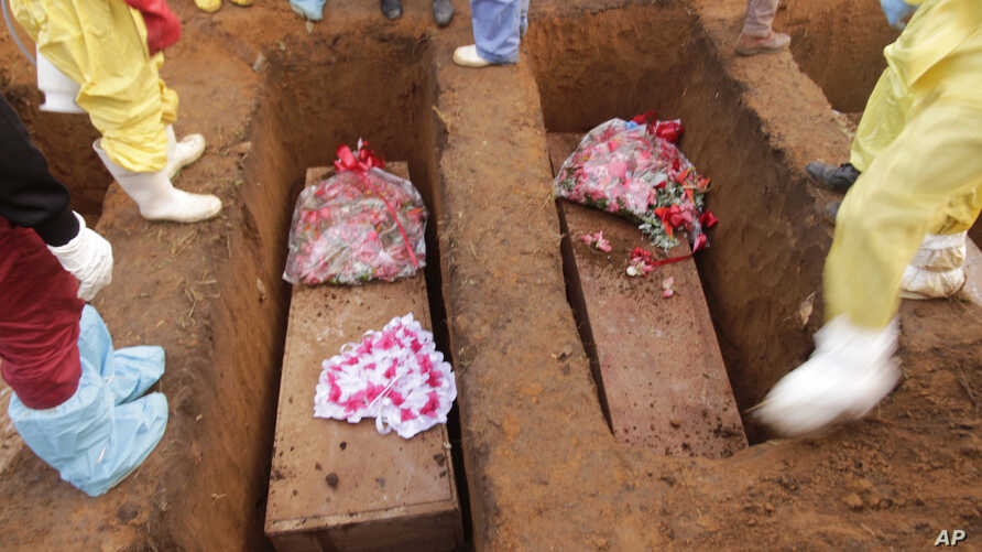 Volunteers bury coffins during a mass funeral for victims of heavy flooding and mudslides in a cemetery in Freetown, Sierra Leone, Aug. 17, 2017.