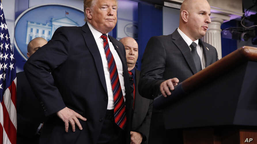 President Donald Trump, left, listens as Brandon Judd, president of the National Border Patrol Council, talks about border security after making a surprise visit to the press briefing room of the White House in Washington, Jan. 3, 2019.
