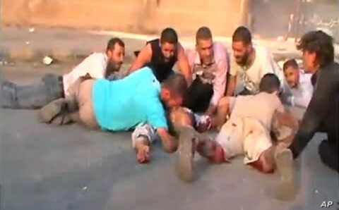 An image grab from a video uploaded on YouTube on July 31, 2011 shows Syrians seeking cover from shooting allegedly by security forces in the city of Hama.