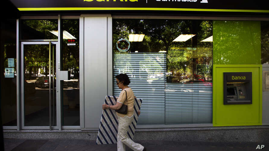 woman walks by an ATM cash machine at a branch of the Bankia bank in Madrid, June 6, 2012.