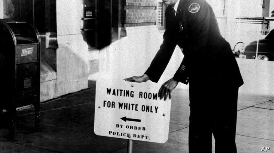 Police Lt. Beavers Armstrong places a segregation sign in front of the Illinois Central Railroad Jan. 9, 1956, after the railroad removed segregation signs from waiting rooms in compliance with an Interstate Commerce Commission order.