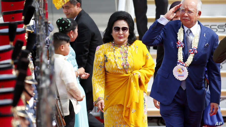 FILE - Malaysian Prime Minister Najib Razak, right, salutes the troops as he arrives with his wife, Rosmah Mansor, at Clark International Airport in Clark, Pampanga province, north of Manila, Philippines, Nov. 12, 2017.