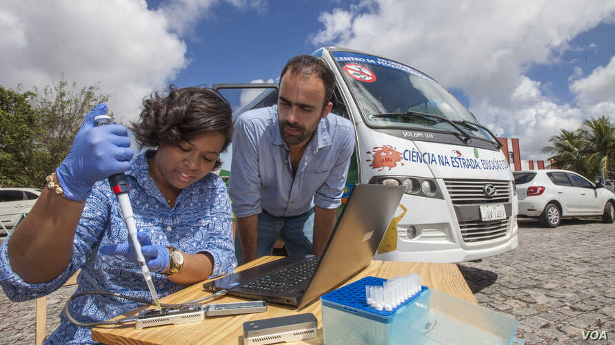 Jaqueline Goes de Jesus (Fundacao Oswaldo Cruz, Salvador), left, and Nuno Faria (University of Oxford, UK) use the Oxford Nanopore MinION device in front of the minibus equipped with a lab, in Joao Pessoa, Brazil. (Courtesy - Ricardo Funari)